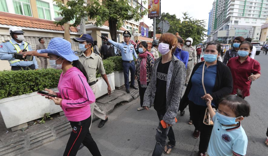Cambodian court security personnel direct relatives who were called on to attend a trial as they arrive at Phnom Penh Municipal Court, in Phnom Penh, Cambodia, Thursday, Nov. 26, 2020. A Cambodian court on Thursday began hearing the cases of nearly 130 opponents and government critics charged with treason for taking part in nonviolent political activities over the past three years, in what one of them described as a sham trial. (AP Photo/Heng Sinith)