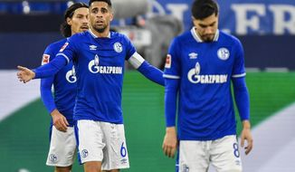 In this Saturday, Nov. 21, 2020 picture Schalke's Omar Mascarell, center, reacts during the German Bundesliga soccer match between VfL Wolfsburg and FC Schalke 04 at the Veltins-Arena in Gelsenkirchen, Germany. (AP Photo/Martin Meissner, Pool)