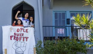 FILE - In this March 30, 2020, file photo, homeless mother Martha Escudero, with her daughters, Mezcli, 8, left, and Victoria, 10, stands on the balcony outside a formerly publicly owned vacant home that her family has moved to in El Sereno neighborhood of Los Angeles. A new group of homeless people who had taken over several empty, state-owned houses in Los Angeles was forcefully removed by California Highway Patrol officers hours later amid protests by dozens of community activists. (AP Photo/Damian Dovarganes, File)