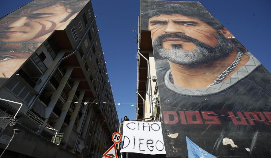 """A woman hangs a sign with writing in Italian reading """"Bye Diego"""" from a building showing a giant mural of soccer legend Diego Maradona, in Naples, southern Italy, Thursday, Nov. 26, 2020. Maradona died Wednesday, Nov. 25, 2020 in Buenos Aires. (AP Photo/Alessandra Tarantino)"""