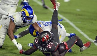 Tampa Bay Buccaneers running back Ronald Jones (27) is upended by Los Angeles Rams middle linebacker Micah Kiser (59) and defensive back Darious Williams (31) during the first half of an NFL football game Monday, Nov. 23, 2020, in Tampa, Fla. (AP Photo/Jason Behnken)