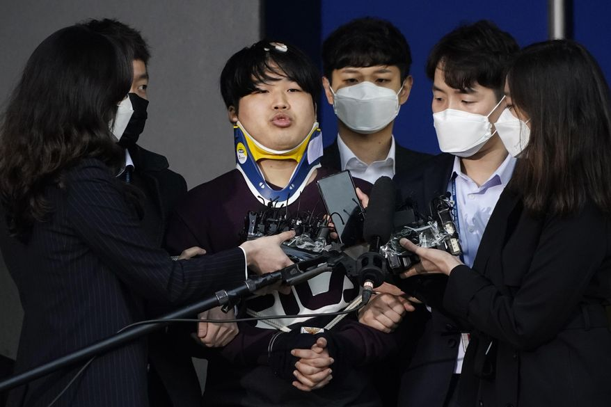 """FILE - In this March 25, 2020, file photo, Cho Ju-bin, center, leader of South Korea's online sexual blackmail ring which is so called """"Nth room,"""" is surrounded by journalists while walking out of a police station as he is transferred to prosecutors' office for further investigation in Seoul, South Korea. The operator of an online chat room in South Korea was sentenced Thursday, Nov. 26, to 40 years in prison for blackmailing women, including minors, into filming sexually explicit video and selling them to others.(Kim Hong-Ji/Pool Photo via AP, File)"""