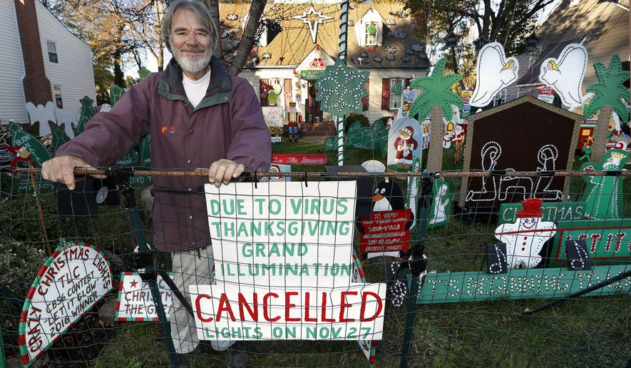 """Al Thompson has posted a sign at his """"tacky light"""" house in Glen Allen, Va., notifying visitors that the Grand Illumination event on Thanksgiving has been cancelled. He has posted another sign saying visitors are limited to 25 people at one time, as per the Gov. Ralph Northam's mandate. Photo was taken on Friday, Nov. 20, 2020. (Alexa Welch Edlund/Richmond Times-Dispatch via AP)"""