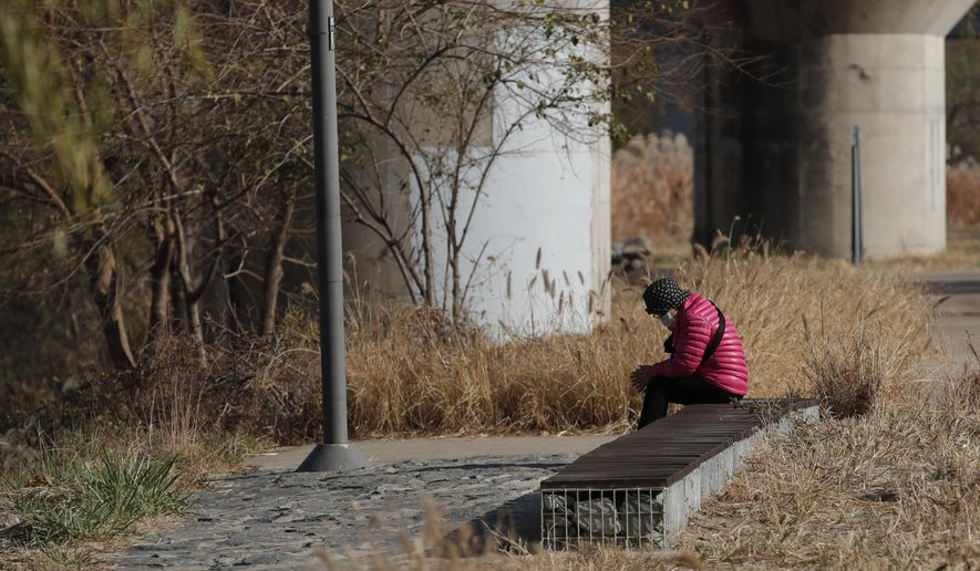 A woman wearing a face mask as a precaution against the coronavirus, sits on a bench while maintaining social distancing at a park in Seoul, South Korea, Thursday, Nov. 26, 2020. (AP Photo/Lee Jin-man)