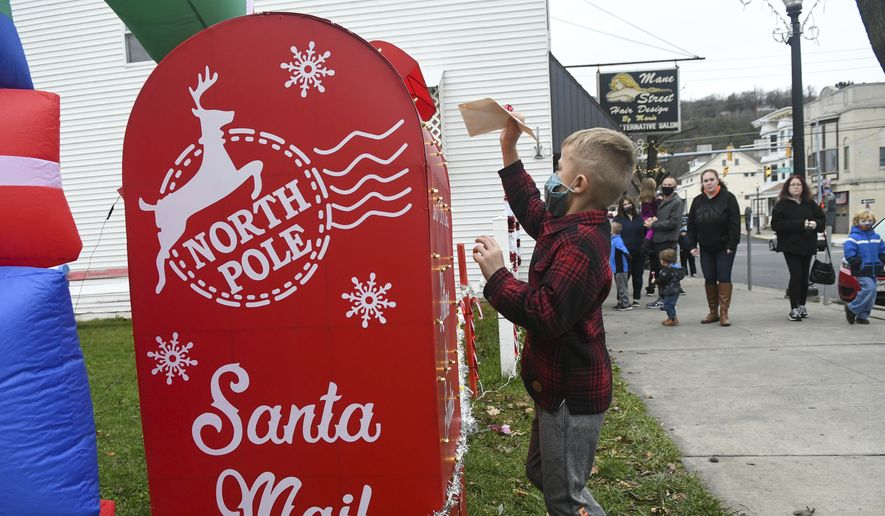 "Bryden Yarnitsky, 6, of Ringtown, Pa., puts his letter to Santa Claus in the North Pole mailbox at the Legion Memorial Garden at the Anthony P. Damato American Legion Medal of Honor Post 792 during the ""Welcoming Santa and The Christmas Season to Shenandoah"" parade in Shenandoah, Pa., on Friday, Nov. 27, 2020. (Jacqueline Dormer/Republican Herald via AP) **FILE**"