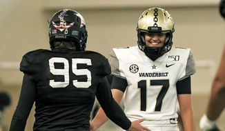 In this image provided by Vanderbilt Athletics, Vanderbilt kicker Sarah Fuller, right, slaps hands with a teammate during NCAA college football practice, Wednesday, Nov. 25, 2020, in Nashville, Tenn. Fuller, a goalkeeper on the Commodores' women's soccer team, will don a football uniform on Vanderbilt's sideline and she is poised to become the first woman to play in a Power 5 game when the Commodores take on Missouri.  (Vanderbilt Athletics via AP)