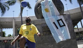 """Marcio Pereira, 57, who likes to go by the nickname """"Pele"""" juggles a soccer ball next to a monument adorned with a national Argentine flag bearing the No. 10, placed there by a mourner as a tribute to Diego Maradona, outside the Maracana stadium in Rio de Janeiro, Brazil, Thursday, Nov. 26, 2020. Maradona died on Wednesday at the age of 60 of a heart attack in a house outside Buenos Aires where he recovered from a brain operation. (AP Photo/Silvia Izquierdo)"""