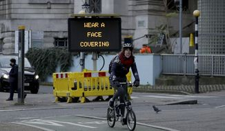 A woman cycles on a Brompton folding bicycle past a sign outside Waterloo Station reminding people they are required to wear face coverings inside the station and whilst traveling on trains, in London, during England's second coronavirus lockdown, Friday, Nov. 20, 2020. (AP Photo/Matt Dunham)