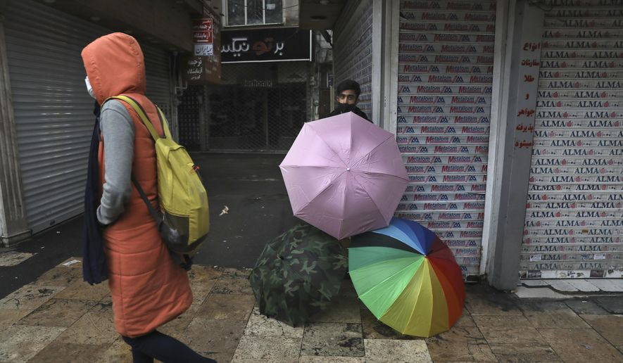 A vendor sells umbrellas outside closed shops in northern Tehran, Iran, Sunday, Nov. 22, 2020. Iran on Saturday shuttered businesses and curtailed travel between its major cities, including the capital of Tehran, as it grapples with the worst outbreak of the coronavirus in the Mideast region. (AP Photo/Vahid Salemi)