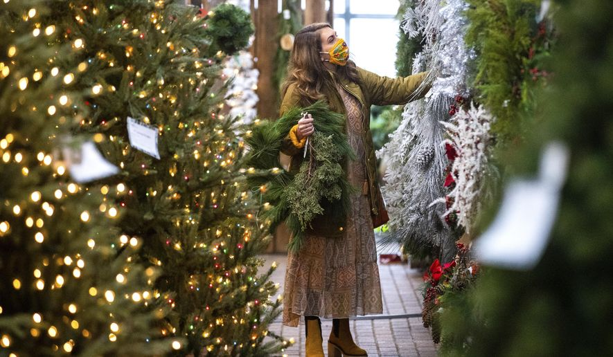 Amanda Perrone shops for Christmas decorations on Black Friday, at Corky's Garden Path Greenhouse in Scott Twp., Pa. on Friday, Nov. 27, 2020. (Christopher Dolan/The Times-Tribune via AP)