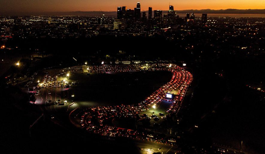 """FILE - In this Nov 18, 2020, file aerial photo, motorists wait in long lines to take a coronavirus test in a parking lot at Dodger Stadium in Los Angeles. The Los Angeles County has announced a new stay-home order as coronavirus cases surge out of control in the nation's most populous county. The three-3 week order take effect Monday, Nov. 30, 2020.  The order advises residents to stay home """"as much as possible"""" and to wear a face covering when they go out. It bans people from gathering with people who aren't in their households, whether publicly or privately. (AP Photo/Ringo H.W. Chiu, File)"""