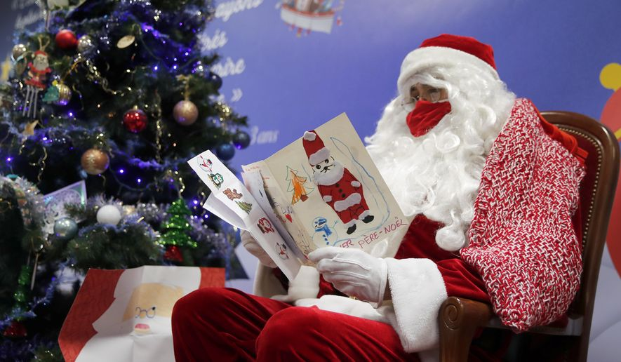 """A postal worker dressed as Santa, reads letters to addressed to """"Pere Noel"""" - Father Christmas in French -  decorated with love hearts, stickers and glitter, in Libourne, southwest France, Monday, Nov. 23, 2020. Letters pouring by the tens of thousands into Santa's mailbox offer a glimpse into the worries and hopes of children awaiting a pandemic-hit Christmas. Along with usual pleas for toys and gadgets, kids are also mailing requests for vaccines, for visits from grandparents, for life to return to the way it was. The office estimates that one letter in three mentions the pandemic. (AP Photo/Francois Mori)"""