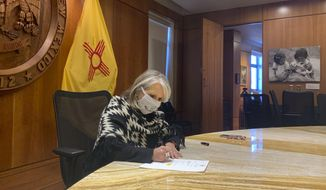 In this photo provided by the New Mexico Office of the Governor, Gov. Michelle Lujan Grisham signs a $330 million economic relief package aimed at helping small businesses and out-of-work New Mexicans while at the State Capitol, Wednesday, Nov. 25, 2020 in Santa Fe, N.M. (New Mexico Office of the Governor via AP)