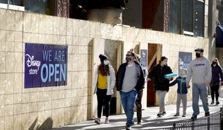 Shoppers pass Saturday, Nov. 28, 2020, an open Disney Store that is still partially boarded up from recent vandalism on Chicago's famed Magnificent Mile shopping district. (AP Photo/Charles Rex Arbogast)