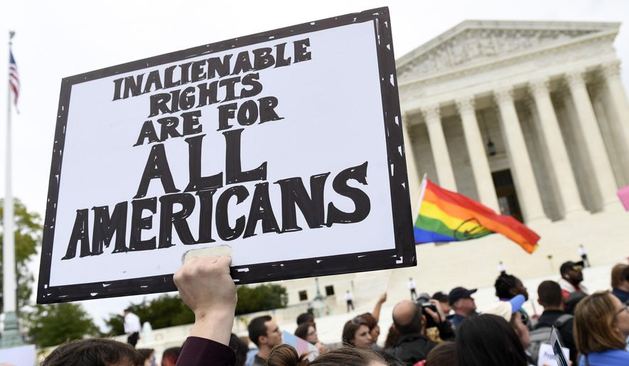 FILE - In this Oct. 8, 2019, file photo, protesters gather outside the Supreme Court in Washington where the Supreme Court is hearing arguments in the first case of LGBT rights since the retirement of Supreme Court Justice Anthony Kennedy.  As vice president in 2012, Joe Biden endeared himself to many LGBTQ Americans by endorsing same-sex marriage even before his boss, President Barack Obama. Now, as president-elect, Biden is making sweeping promises to LGBTQ activists, proposing to carry out virtually every major proposal on their wish lists.   (AP Photo/Susan Walsh, File)