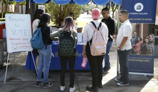 FILE - In this Sept. 24, 2019 file photo students at Phoenix College gather to fill out voter registration forms on National Voter Registration Day on campus, in Phoenix. Immigrant-rights and grassroots organizations that have been mobilizing Latinos in Arizona for nearly two decades helped propel Joe Biden to victory in a traditionally conservative state.  (AP Photo/Ross D. Franklin,File)