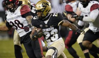 Colorado running back Jarek Broussard, front, runs for a short gain as San Diego State linebacker Andrew Aleki pursues during the second half of an NCAA college football game Saturday, Nov. 28, 2020, in Boulder, Colo. (AP Photo/David Zalubowski)