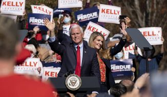 In this Nov. 20, 2020, file photo Vice President Mike Pence and Kelly Loeffler wave to the crowd during a Defend the Majority Rally in Canton, Ga. U.S. Sen. Kelly Loeffler waves behind Pence. (AP Photo/Ben Gray, File) ** FILE **