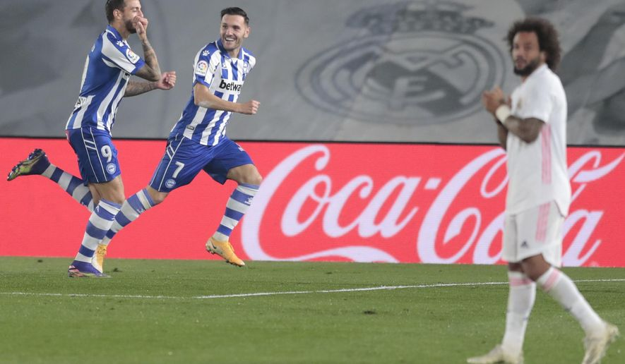 Alaves' Joselu, left, celebrates after scoring his side's second goal during the Spanish La Liga soccer match between Real Madrid and Alaves at Alfredo di Stefano stadium in Madrid, Spain, Saturday, Nov. 28, 2020. (AP Photo/Bernat Armangue)