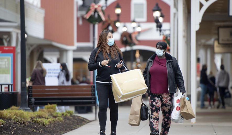 Debra Hearn from Penn Hills, Pa., and her sister Renee Bell, from Stanton Heights, Pa., walk to their car after a morning of shopping at Tanger Outlets in Washington, Pa., Friday, Nov. 27, 2020. The two started their traditional after Thanksgiving shopping trip at 5 a.m. (Pam Panchak/Post-Gazette via AP)