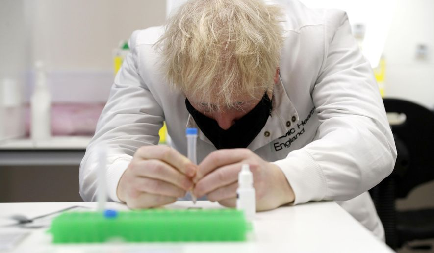 Britain's Prime Minister Boris Johnson, wearing a mask because of the coronavirus,  has a close look at a sample at the Lateral Flow Testing Laboratory during a visit to the Public Health England site at Porton Down science park near Salisbury, southern England, on Friday Nov. 27, 2020. (Adrian Dennis/Pool via AP)