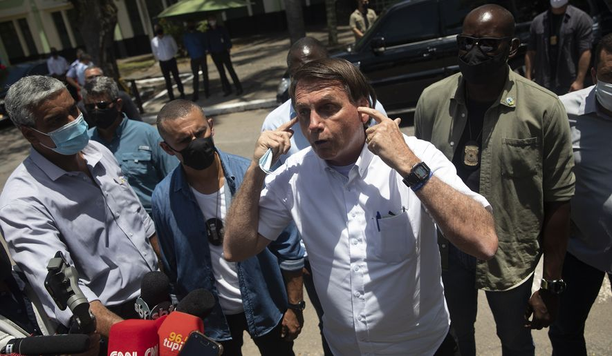 """Brazil's President Jair Bolsonaro talks with the media outside a polling station, after voting during the run-off municipal elections in Rio de Janeiro, Brazil, Sunday, Nov. 29, 2020. Bolsonaro, who sometimes has embraced the label """"Trump of the Tropics,"""" said Sunday he'll wait a little longer before recognizing the U.S. election victory of Joe Biden, while also echoing President Donald Trump's allegations of irregularities in the U.S. vote. (AP Photo/Silvia Izquierdo) ** FILE **"""