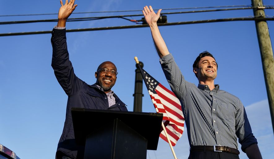 In this Nov. 15, 2020, file photo Georgia Democratic candidates for U.S. Senate Raphael Warnock, left, and Jon Ossoff, right, gesture toward a crowd during a campaign rally in Marietta, Ga. (AP Photo/Brynn Anderson, File)