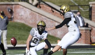 Vanderbilt's Sarah Fuller, right, kicks off as Ryan McCord (27) holds to start the second half of an NCAA college football game against Missouri Saturday, Nov. 28, 2020, in Columbia, Mo. With the kick, Fuller became the first female to play in a Southeastern Conference football game. (AP Photo/L.G. Patterson) **FILE**