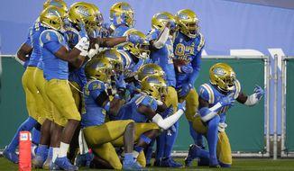 UCLA players pose for photos after intercepting an Arizona pass during the second half of an NCAA college football game Saturday, Nov. 28, 2020, in Pasadena, Calif. (AP Photo/Marcio Jose Sanchez)