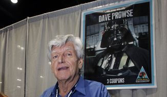 In this file photo dated Saturday, May 26, 2007, actor David Prowse, who was the man in the black Darth Vader suit in the first Star Wars film, signs autographs at Star Wars Celebration IV, marking the 30th anniversary of the release of the first film in the Star Wars saga, in Los Angeles, USA.  The British actor, Prowse who played Darth Vader in the original Star Wars trilogy, has died aged 85 on Saturday, according to an announcement by his agent Sunday, Nov. 29, 2020. (AP Photo/Reed Saxon, FILE)