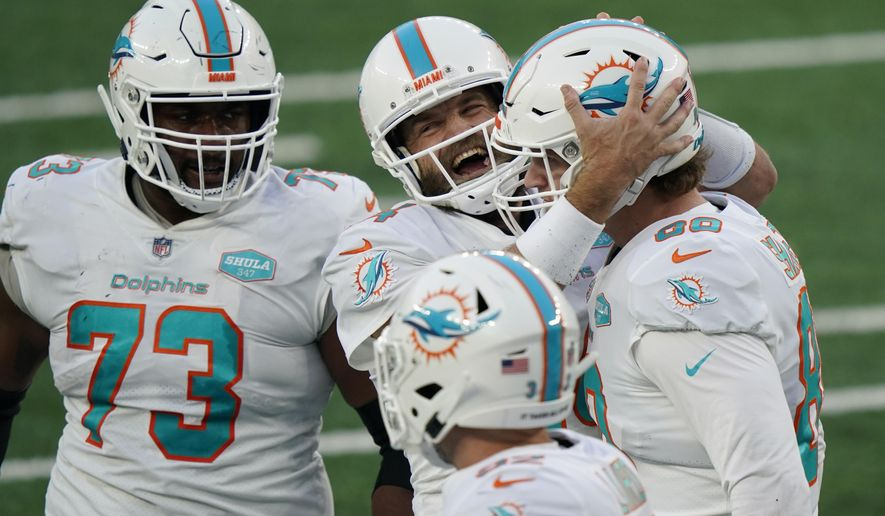 Miami Dolphins quarterback Ryan Fitzpatrick, center, celebrates a touchdown with Adam Shaheen, right, during the second half of an NFL football game against the New York Jets, Sunday, Nov. 29, 2020, in East Rutherford, N.J. (AP Photo/Corey Sipkin)