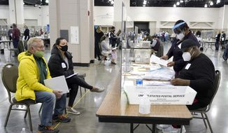 In this file photo, election workers, right, verify ballots as recount observers, left, watch during a Milwaukee hand recount of presidential votes at the Wisconsin Center, Friday, Nov. 20, 2020, in Milwaukee. Wisconsin finished a partial recount of its presidential results on Sunday, Nov. 29, 2020 confirming Democrat Joe Biden's victory over President Donald Trump in the key battleground state. Trump vowed to challenge the outcome in court. (AP Photo/Nam Y. Huh)  **FILE**