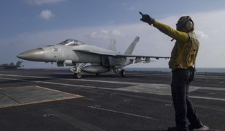 In this photo released by the U.S. Navy, Aviation Boatswain's Mate 3rd Class Marnell Maglasang, from La Puente, Calif., directs an F/A-18E Super Hornet on the flight deck of the aircraft carrier USS Nimitz in the Arabian Sea, Friday Nov. 27, 2020.  (Mass Communication Specialist 3rd Class Cheyenne Geletka/U.S. Navy via AP)  **FILE**