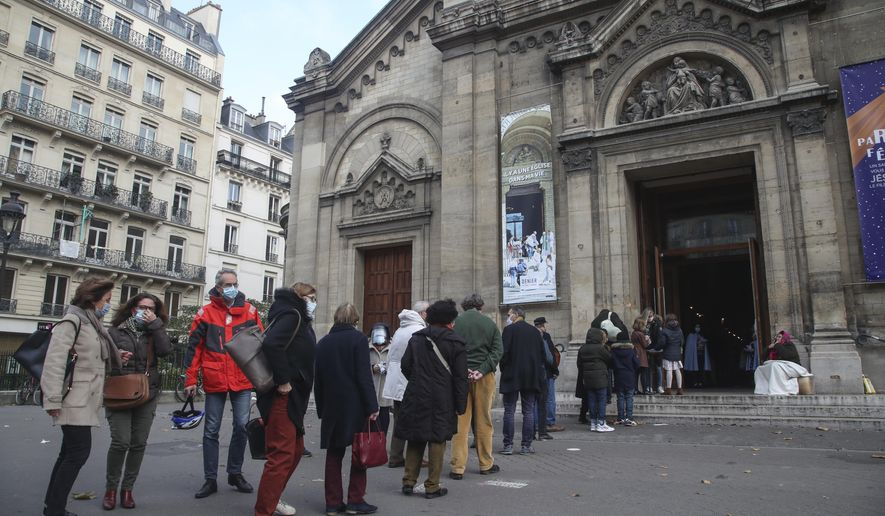 Church-goers wearing face masks as a precaution against the coronavirus lineup outside the Notre-Dame-des-Champs church in Paris, Sunday, Nov. 29, 2020. French churches, mosques and synagogues can open their doors again to worshippers - but only a few of them, as France cautiously starts reopening after a second virus lockdown. Some churches may defy the 30-person limit they feel as too unreasonable, and other sites may stay closed until they can reopen for real. (AP Photo/Michel Euler)