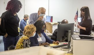 Election officials and observers examine ambiguous ballots during the Georgia presidential election recount at a Richmond County elections facility in south Augusta, Ga., Monday morning, Nov. 30, 2020 (Michael Holahan/The Augusta Chronicle via AP) ** FILE **