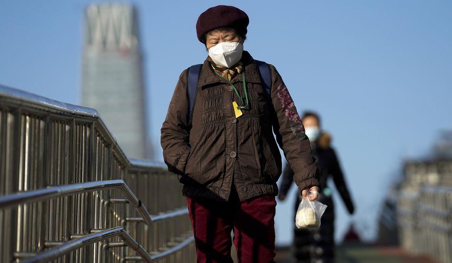 Women wearing face masks to help curb the spread of the coronavirus walk along a pedestrian bridge in Beijing, Monday, Nov. 30, 2020. (AP Photo/Andy Wong)