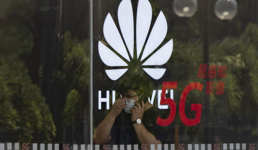 FILE - In this Wednesday, July 15, 2020 file photo, a worker wearing a mask to curb the spread of the coronavirus speaks on the phone near the Huawei logo in a store in Beijing. U.K. telecom companies won't be allowed to install Huawei equipment in their high-speed 5G networks after September 2021, the British government said Monday Nov. 30, 2020, hardening its line against the Chinese technology company. (AP Photo/Ng Han Guan, File)