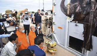 "The container holding Kaavan the elephant is blessed by monks during its arrival from Pakistan at the Siem Reap International Airport, Cambodia, Monday, Nov. 30, 2020. Kaavan, dubbed the ""world's loneliest elephant"" after languishing alone for years in a Pakistani zoo, has arrived in Cambodia where a sanctuary with the much-needed company of other elephants awaits him. (Pool Photo via AP)"
