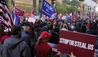 """Supporters of President Donald Trump protest in front of a local hotel where Arizona Republicans have scheduled a meeting as a """"fact-finding hearing"""" to discuss the election, featuring members of Trump's legal team and Arizona legislators, Monday, Nov. 30, 2020, in Phoenix. (AP Photo/Ross D. Franklin) **FILE**"""