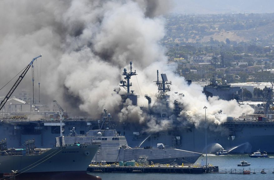 FILE - In this July 12, 2020, file photo, smoke rises from the USS Bonhomme Richard at Naval Base San Diego in San Diego, after an explosion and fire onboard the ship at Naval Base San Diego. The Navy on Monday, Nov. 30, 2020, said that it will decommission the warship docked off San Diego after suspected arson caused extensive damage, making it too expensive to restore. (AP Photo/Denis Poroy, File)
