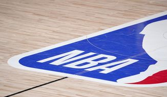 In this Sept. 2, 2020, file photo, the NBA logo is displayed at center court during an NBA first-round playoff basketball game between the Houston Rockets and Oklahoma City Thunder in Lake Buena Vista, Fla. NBA training camps open around the league Tuesday, Dec. 1, 2020, though on-court sessions will be limited to individual workouts and only for those players who have gotten three negative coronavirus test results back in the last few days. (AP Photo/Mark J. Terrill, File) **FILE**