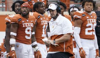 FILE - In this Friday, Nov. 27, 2020, file photo, Texas head coach Tom Herman, center, walks on the sideline during the second half of an NCAA college football game against Iowa State in Austin, Texas. Herman batted away questions about his future with the program on Monday, Nov. 30, 2020, and insisted on trying to keep the focus on the Longhorns' players trying to win their last two games of the season. (AP Photo/Eric Gay, File)