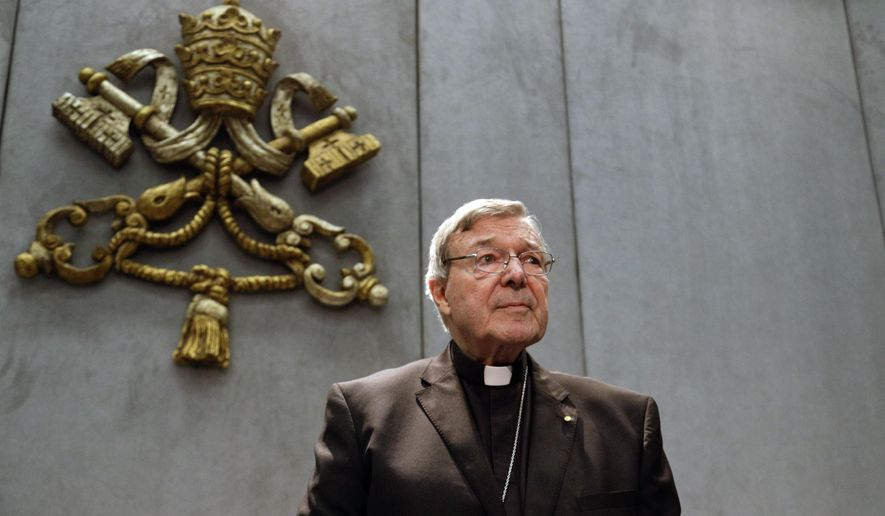 FILE - In this June 29, 2017, file photo, Cardinal George Pell prepares to make a statement, at the Vatican. Cardinal George Pell, who was convicted and then acquitted of sexual abuse in his native Australia, reflects on the nature of suffering, Pope Francis' papacy and the humiliations of solitary confinement in his jailhouse memoir, according to an advance copy obtained by The Associated Press. (AP Photo/Gregorio Borgia, File)