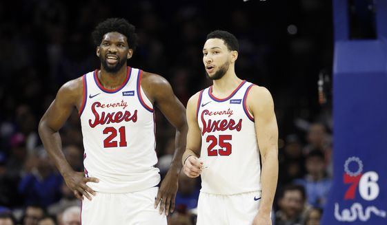In this Dec. 13, 2019, file photo, Philadelphia 76ers' Ben Simmons, right, and Joel Embiid talk during an NBA basketball game against the New Orleans Pelicans in Philadelphia. The 76ers new coach Doc Rivers is set to begin his first training camp with the team trying to unlock the potential of All-Stars Ben Simmons and Joel Embiid.(AP Photo/Matt Slocum, File) **FILE**
