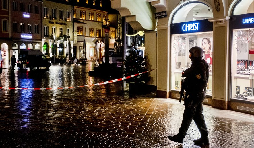 Police officers guard the scene of an incident in Trier, Germany, Tuesday, Dec. 1, 2020. German police say people have been killed and several others injured in the southwestern German city of Trier when a car drove into a pedestrian zone. Trier police tweeted that the driver had been arrested and the vehicle impounded.(AP Photo/Michael Probst)