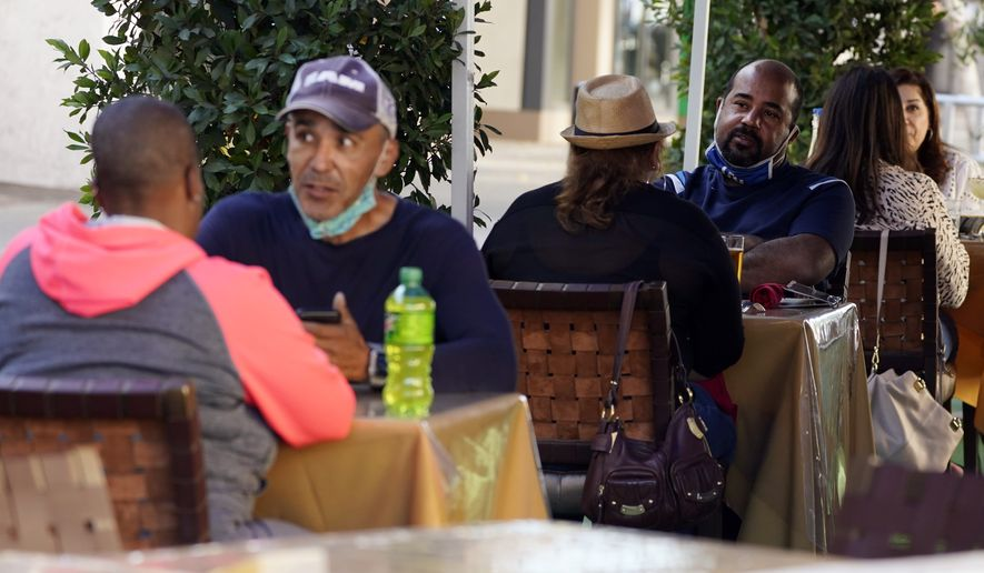People eat lunch outdoors Tuesday, Dec. 1, 2020, in Pasadena, Calif. Pasadena has become an island in the center of the nation's most populous county, where a surge of COVID-19 cases last week led to a three-week end to outdoor dining and California's first stay-home order since the pandemic began to spread across the state in March. The city has its own health department, and can set its own rules, even as Los Angeles County ordered a three-week end to outdoor dining and then a broader stay-home order that took effect Monday. (AP Photo/Marcio Jose Sanchez)