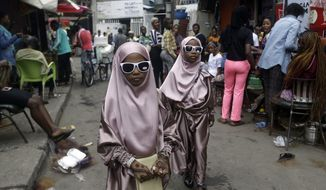 """Muslim girls walk down the street after prayers in Lagos, Nigeria, on July 31, 2020, as Muslims worldwide marked the start of Eid al-Adha, or """"Feast of Sacrifice,"""" in which Muslims slaughter livestock and distribute the meat to the poor. (AP Photo/Sunday Alamba)"""