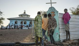 Tigrayan men who fled the conflict in Ethiopia's Tigray region, listen to a priest deliver a sermon during Sunday Mass, at a church near Umm Rakouba refugee camp in Qadarif, eastern Sudan, Nov. 29, 2020. (AP Photo/Nariman El-Mofty)