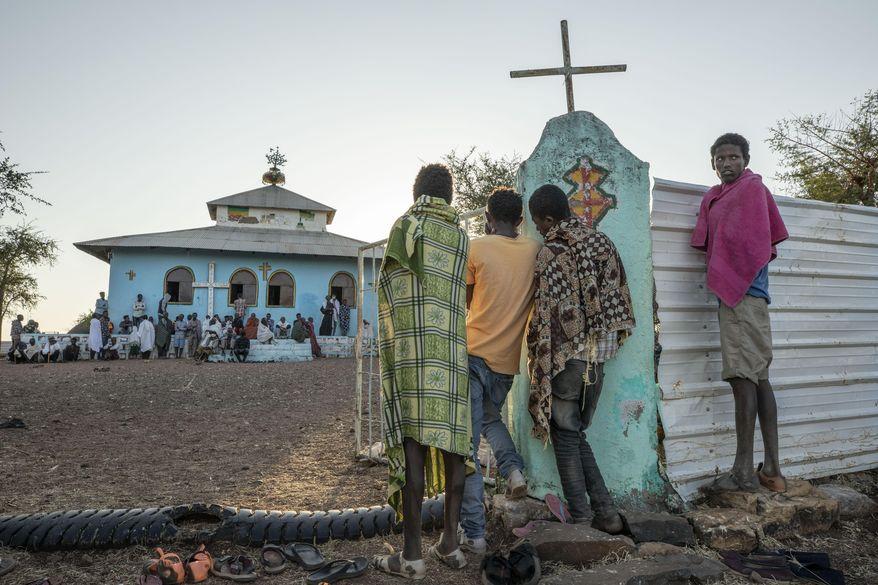 Tigrayan men who fled the conflict in Ethiopia's Tigray region, listen to a priest deliver a sermon during Sunday Mass, at a church near Umm Rakouba refugee camp in Qadarif, eastern Sudan, Nov. 29, 2020. (AP Photo/Nariman El-Mofty)
