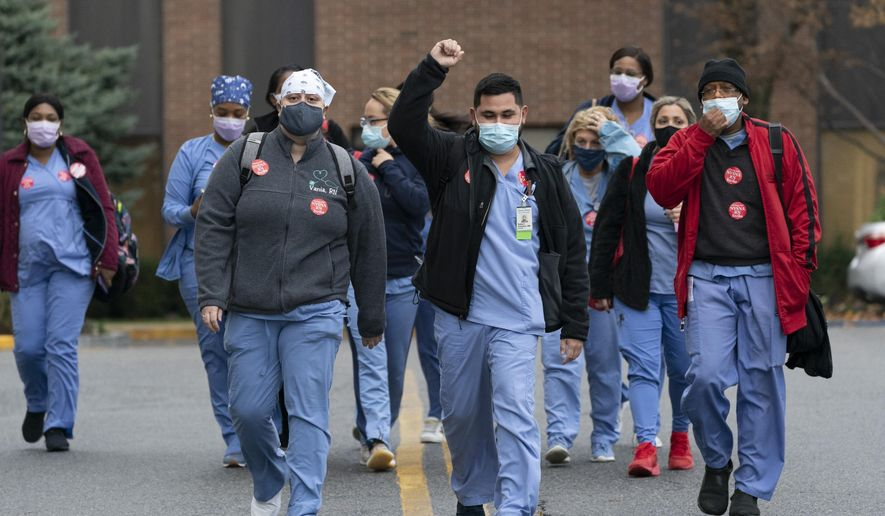 Nurses walk out of Montefiore New Rochelle Hospital to go on strike over safe staffing issues during the coronavirus pandemic, Tuesday, Dec. 1, 2020, in New Rochelle, N.Y. (AP Photo/Mark Lennihan)